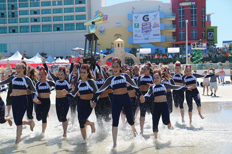 UNH cheerleaders running into the ocean with a trophy