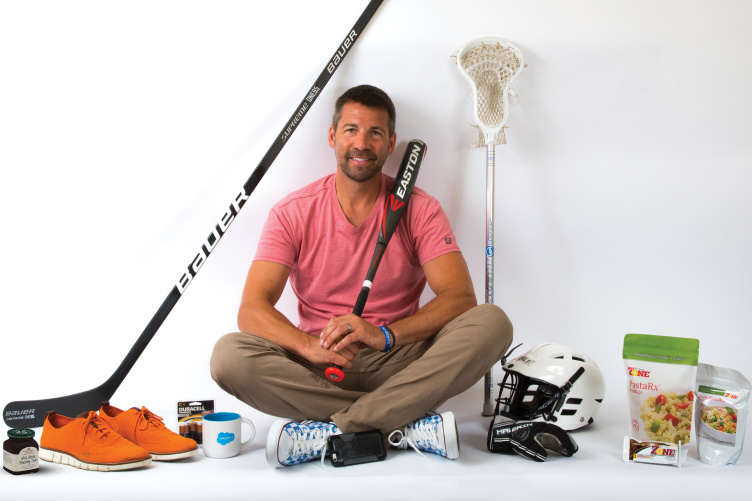 Erik Dodier '92 poses with products created by PixelMEDIA's clients.