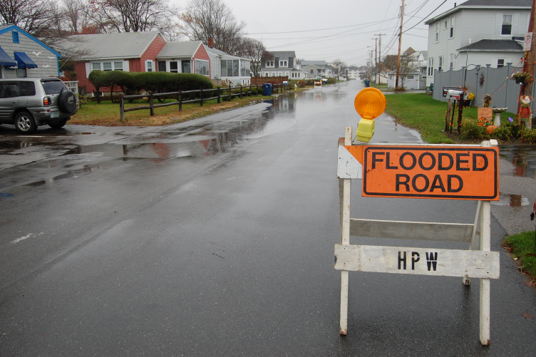 Flooded road with hazard sign in front