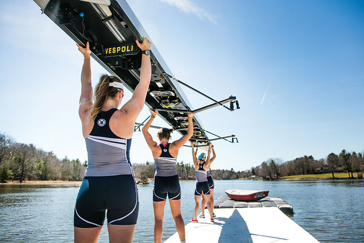 the UNH women's crew team holding up their boat
