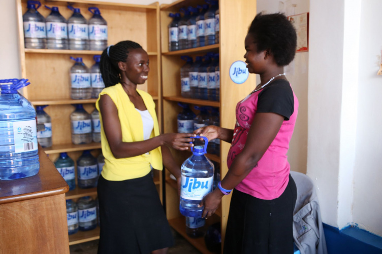A woman purchases water from a Jibu franchisee.