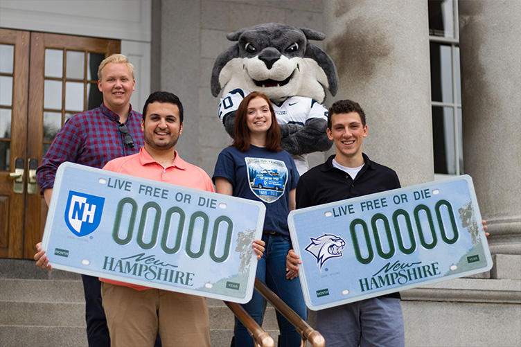 UNH students Jose Calvo of Goffstown, Christian Merheb of Derry, Andrea Plourde of Pembroke and Brennan Pouliot of Goffstown, along with Gnarlz, show off the new UNH license plate decal options on the steps of the State House in Concord