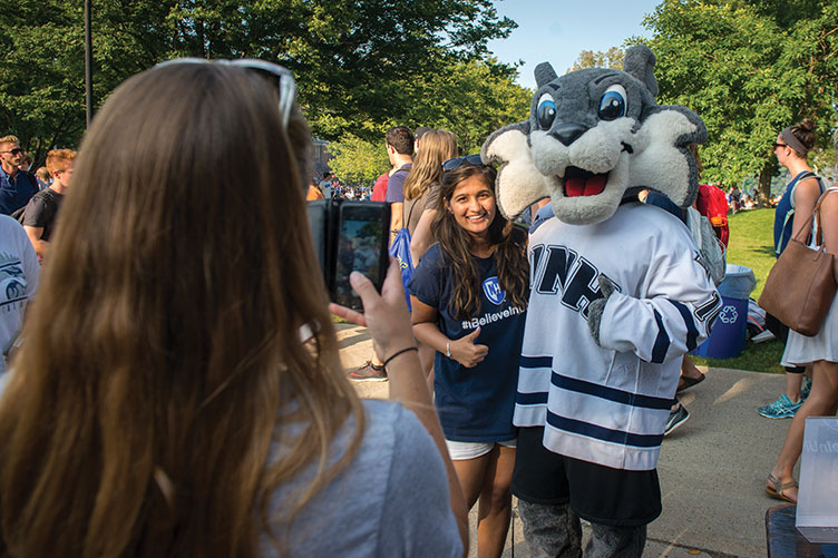 UNH student takes a photo with Wild E. Cat