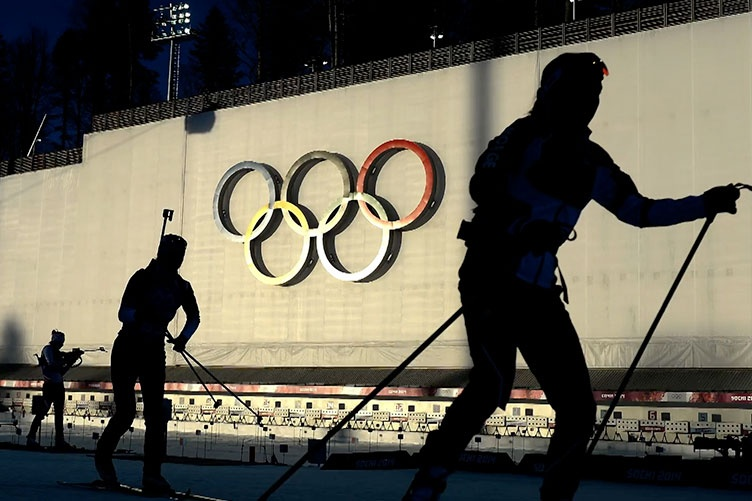 skiers in front of the olympic rings