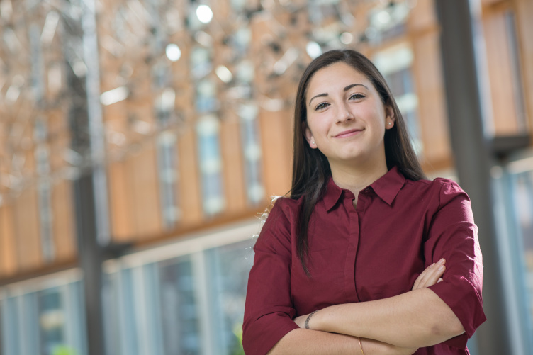 UNH student stands confidently in UNH Paul College Great Hall