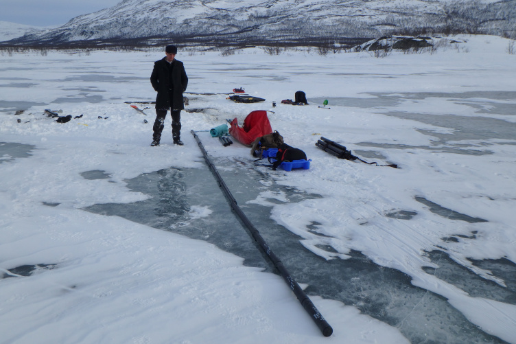 Young man dressed in warm winter clothing stands on frozen lake next to long series of black sediment cores.