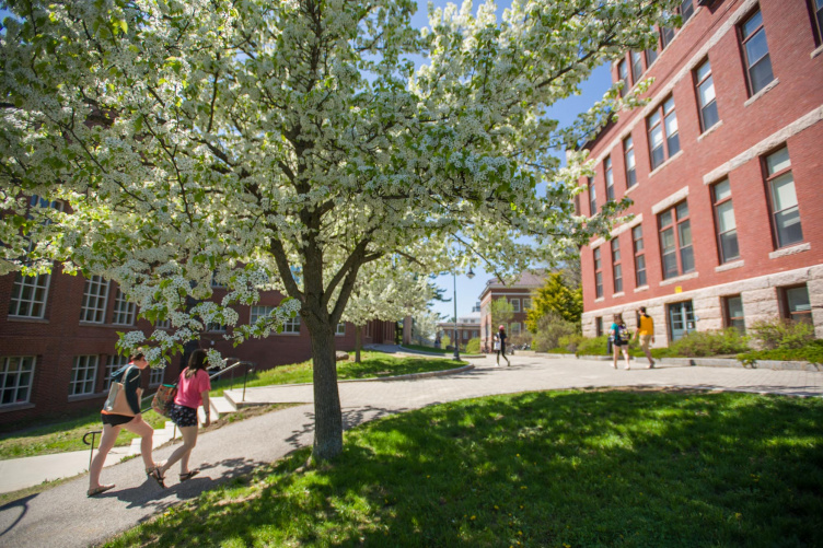 Students walking on a path at UNH's Durham campus, spring 2018