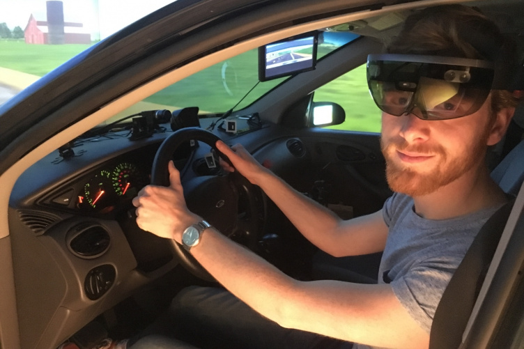 Man sitting in a driving simulator wearing augmeted reality goggles