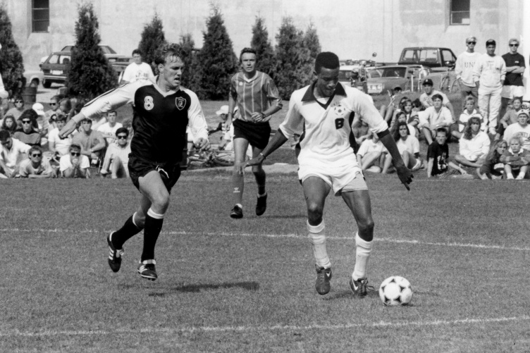 Two college soccer players in a black and white photo from the 1990s