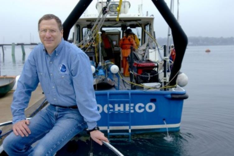 Larry Mayer sits on dock near research vessel.