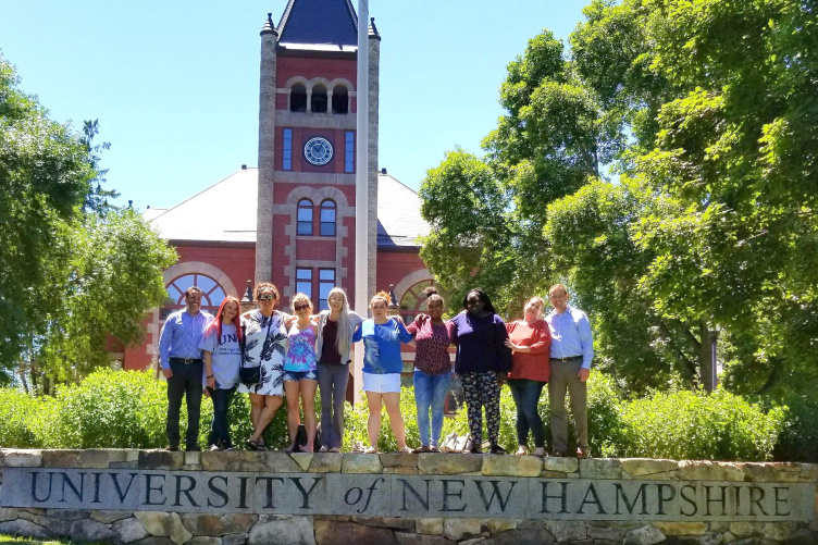 Daniel Silverman and residents of Lydia's House of Hope pose on the UNH wall on the Thompson Hall lawn