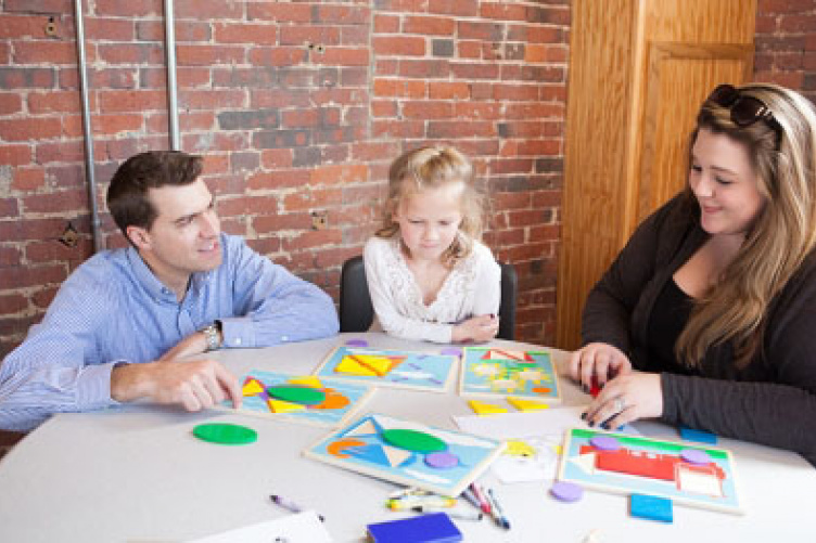 UNH neuropsychology students at a table with a young child