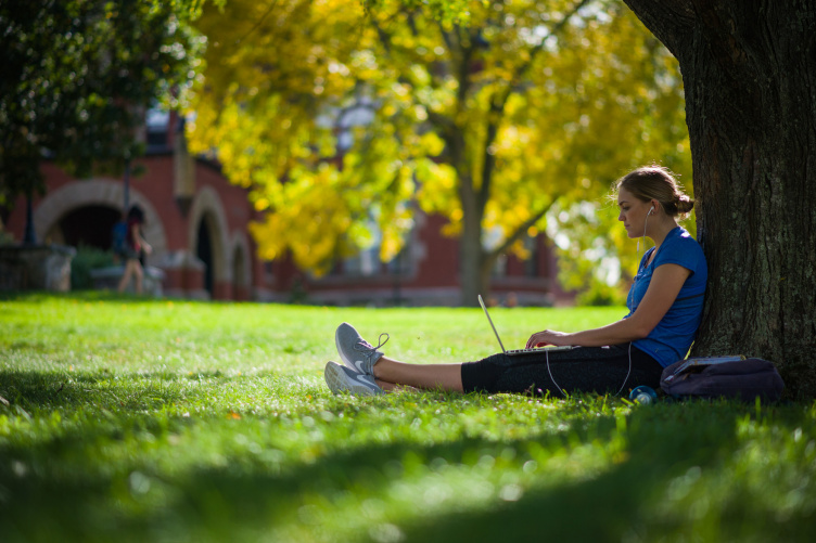 A UNH student sitting against a tree on the Durham campus