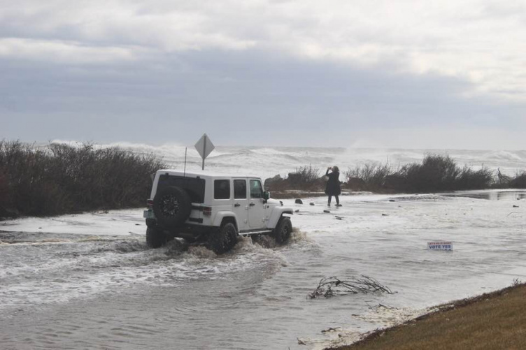 Jeep drives through water on flooded coastal road.