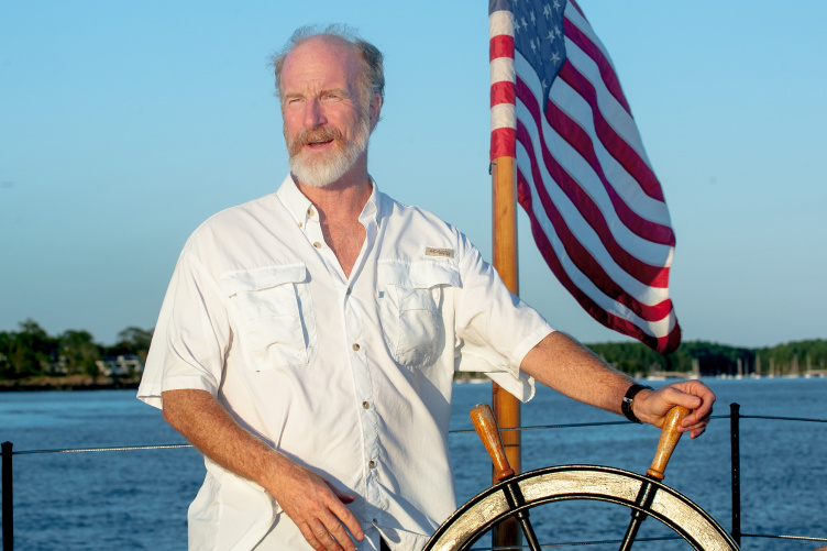 UNH professor of history Jeff Bolster driving a boat