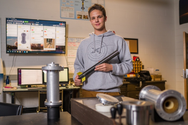 Charlie Nitschelm '20 in a lab with parts of a rocket he's made.