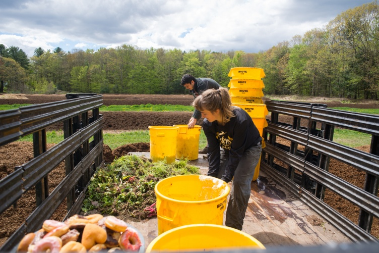 Students loading buckets of dining hall waste to be composted