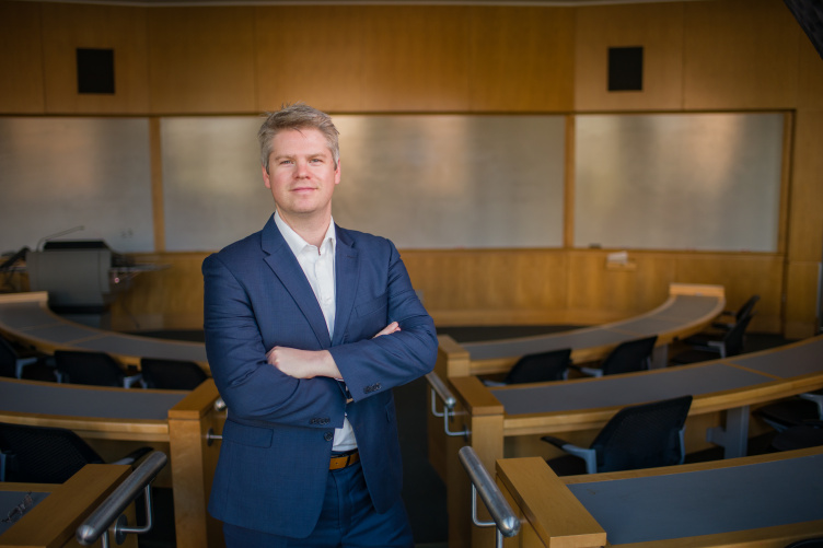 Professor Chris Glynn poses in a Paul College classroom