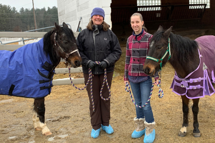 UNH's Brenda K. Hess-McAskill  and Julia Zabkar '21 with two rescue ponies