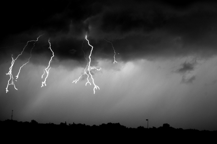 Three flashes of lightning emerge from the same cloud.