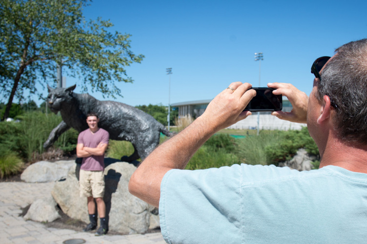 A UNH parent takes a photo of a student at the Wildcat statue