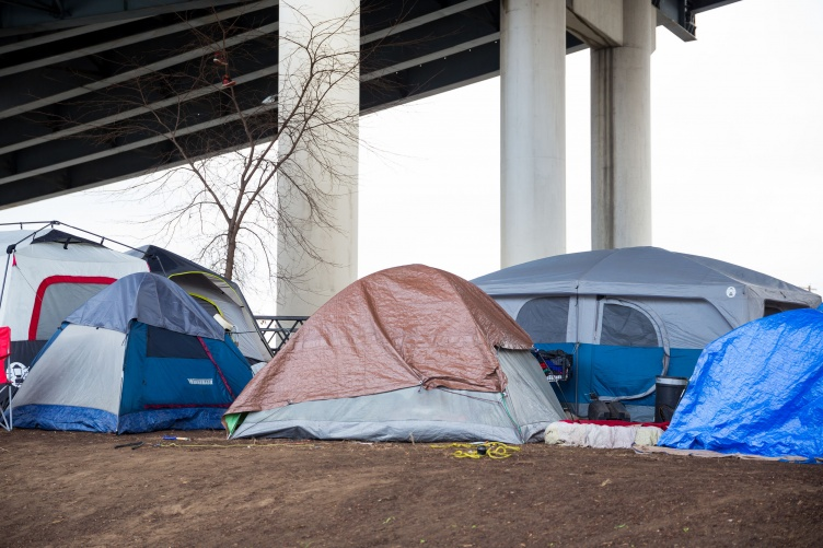 Tent camp of homeless people under a bridge