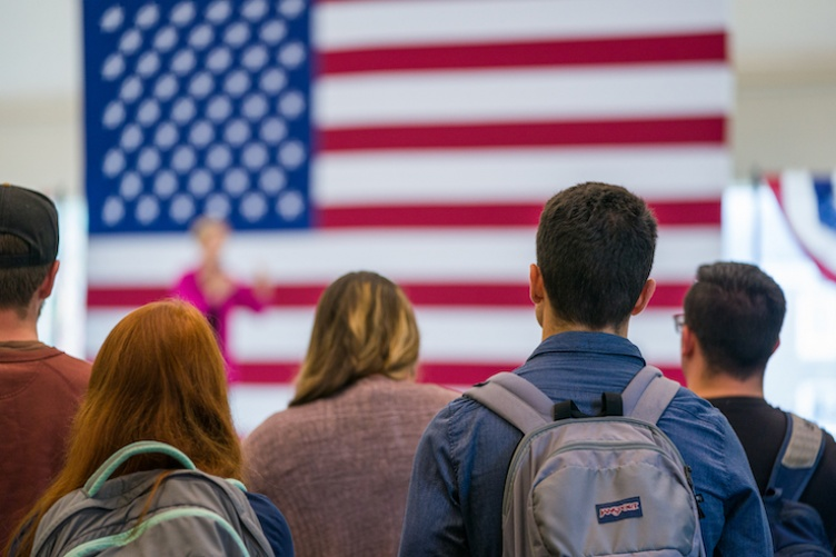 students in front of an American flag