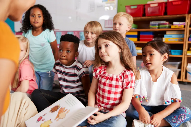 A diverse group of young students listening to their teaching read a book.