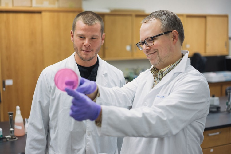 Kyle MacLea teaches student microbiology in lab at UNH Manchester