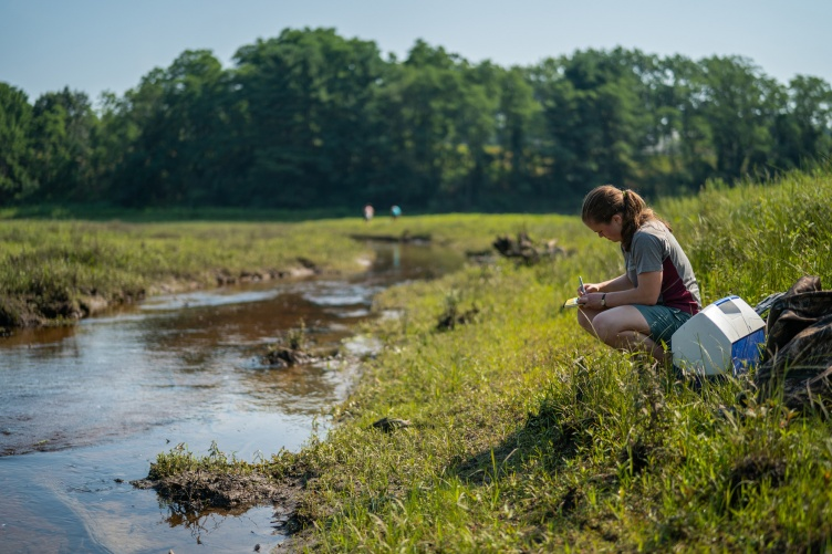 Woman sits by river bank taking notes.