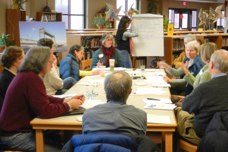 A trained facilitator writes on a large piece of paper while another facilitator leads a discussion at a table of nine participants.