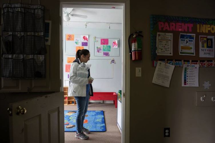 A women waits for a staff member to retrieve her child's belongings