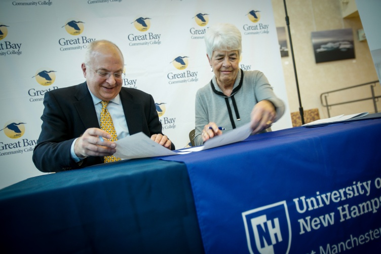 Mike Decelle, dean of UNH Manchester, and Dr. Cathryn Addy, interim president of Great Bay Community College, sign new transfer pathways programs into agreement.