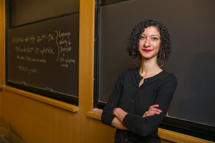 Physics professor Chanda Prescod-Weinstein stands against a chalkboard with arms crossed.
