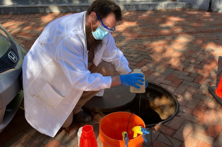 KELLEN SAWYER, A RESEARCH TECHNICIAN LEADING THE UNH SEWAGE MONITORING, RETRIEVES A SAMPLE FROM ONE OF THE MANHOLES