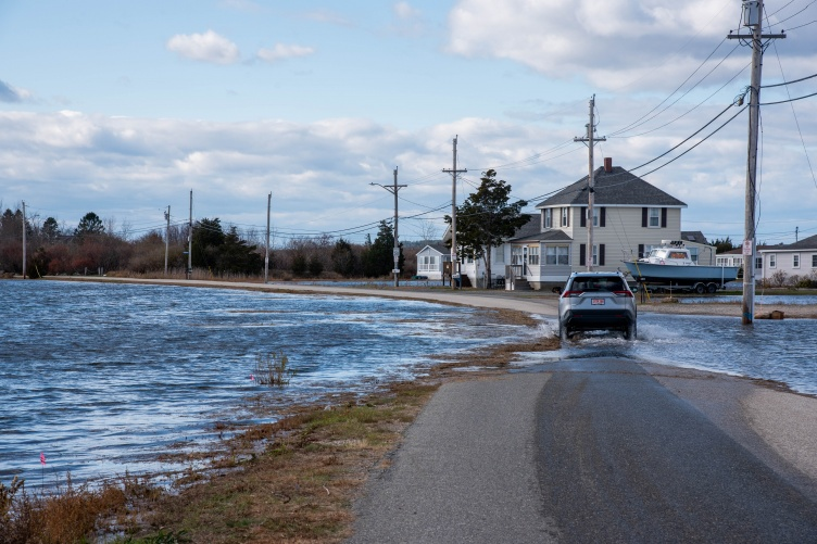 Car drives on flooded road near beach
