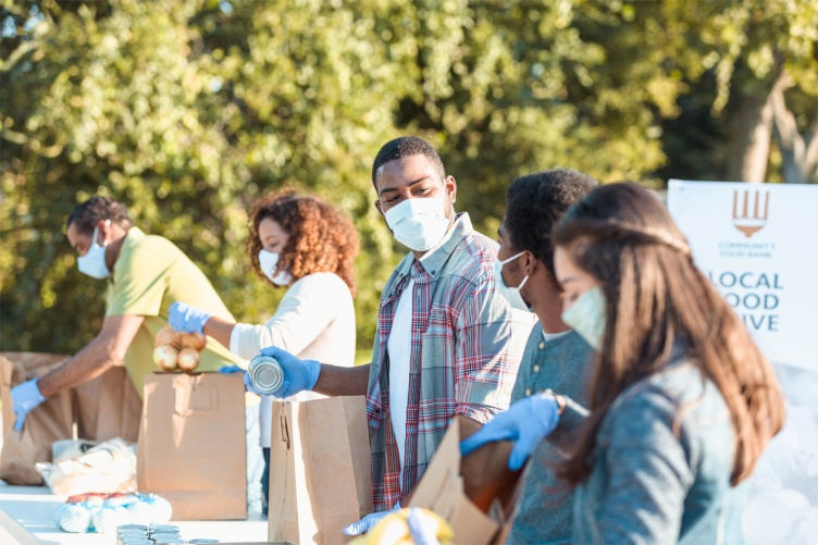 A photo showing a group of nonprofit workers filling food bags at a food drive.