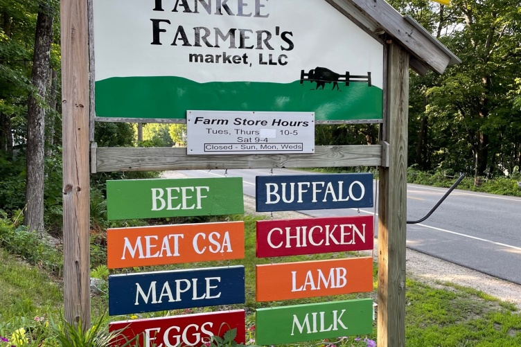A sign showing a local farm store information