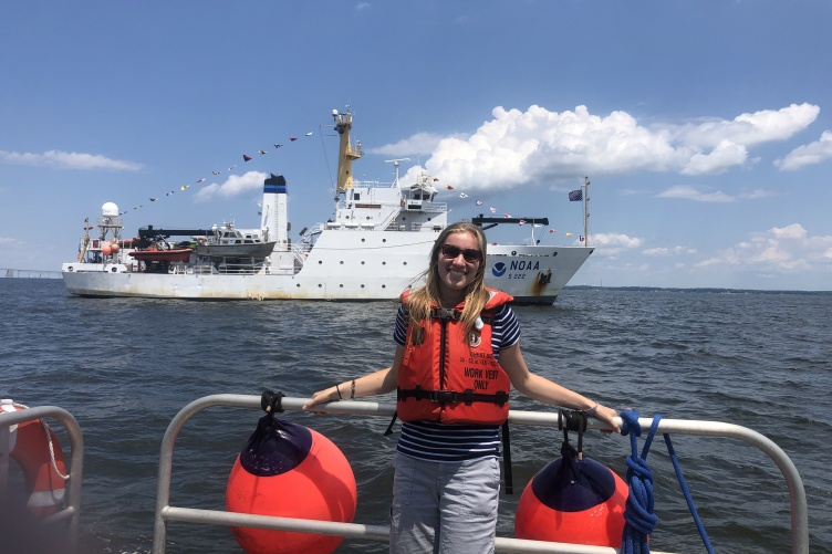 Natalie Cook stands on a ship in front of the Thomas Jefferson hydrographic vessel.