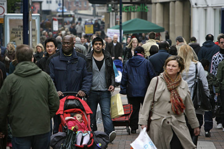 A group of racially and ethically diverse people cross the street in a city