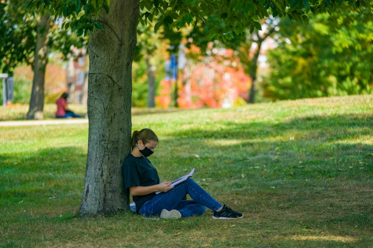 student sitting under tree reading