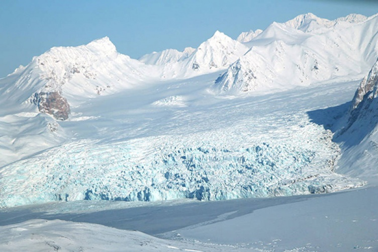A small glacier and snow-covered mountains in Svalbard, Norway.