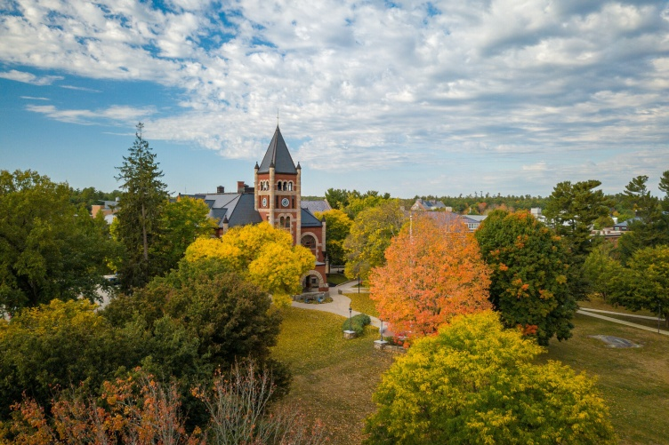 Aerial photo of UNH campus in fall, with bright trees in front of T Hall