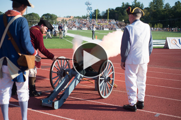 UNH alumnus Dick Dewing '53 firing the cannon at UNH's homecoming football game