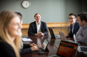 Professor of Marketing Tom Gruen chats with MBA students in a marketing class.