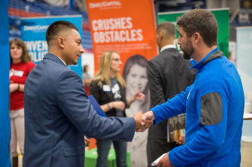 student and employer shake hands at the fall 2017 Career and Internship Fair
