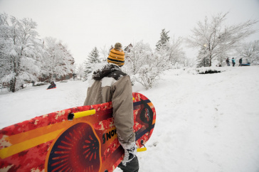 UNH student carrying sled during snowstorm