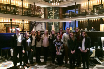 Hospitality management students and alumni pose at a hotel