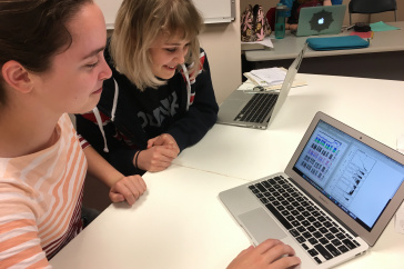 Two young women sit at a table in front of a laptop and smile as they look at colorful graphs on the screen.