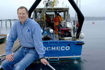 Larry Mayer sits on the edge of a dock in front of a research vessel